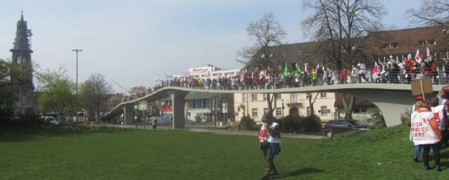 Blick vom Stadtgarten nach Süden zum Freiburger Münster am 27.3.2014 - Demonstrationszug auf der Fussgängerbrücke